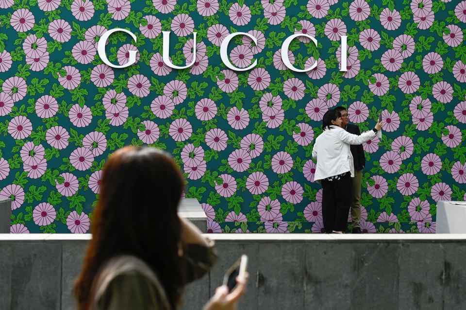 CHINA-LIFESTYLE. People take a picture outside a Gucci store in Beijing.
