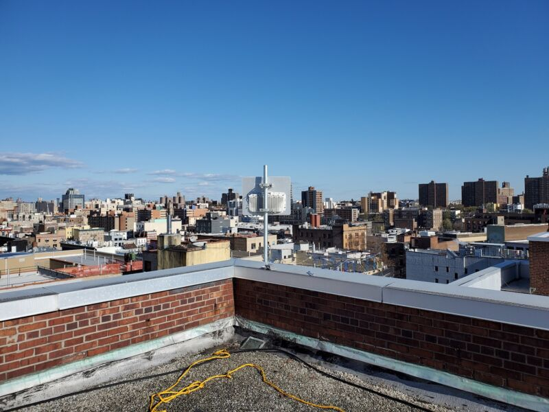 An antenna on a rooftop in the Bronx, with a view of the city during daytime.