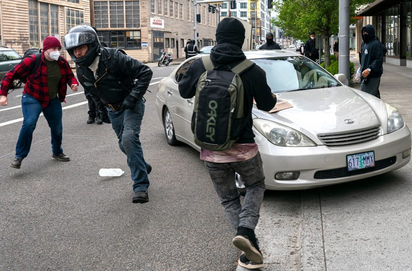 Police declare riot in Portland after May Day protesters break windows